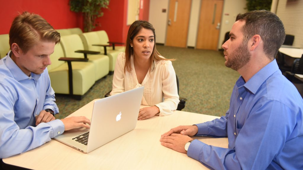students talking with laptop
