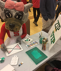 Mrs. Wuf takes some time for art at Jacob Britt's ZipToVip table.