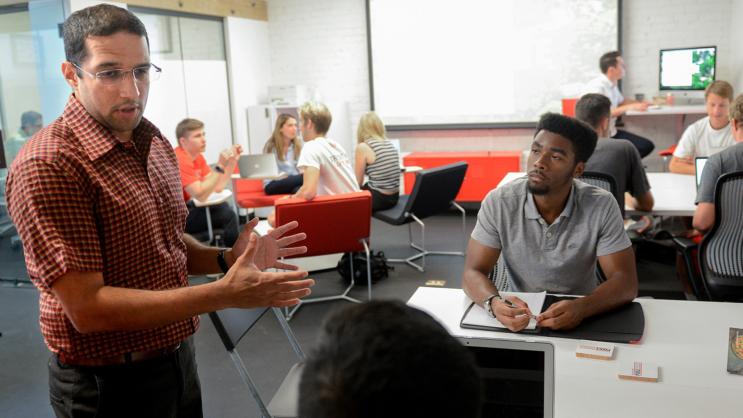 Assistant Professor of Entrepreneurship Nachiket Bhawe with students at the NC State Entrepreneurship Clinic at HQ Raleigh
