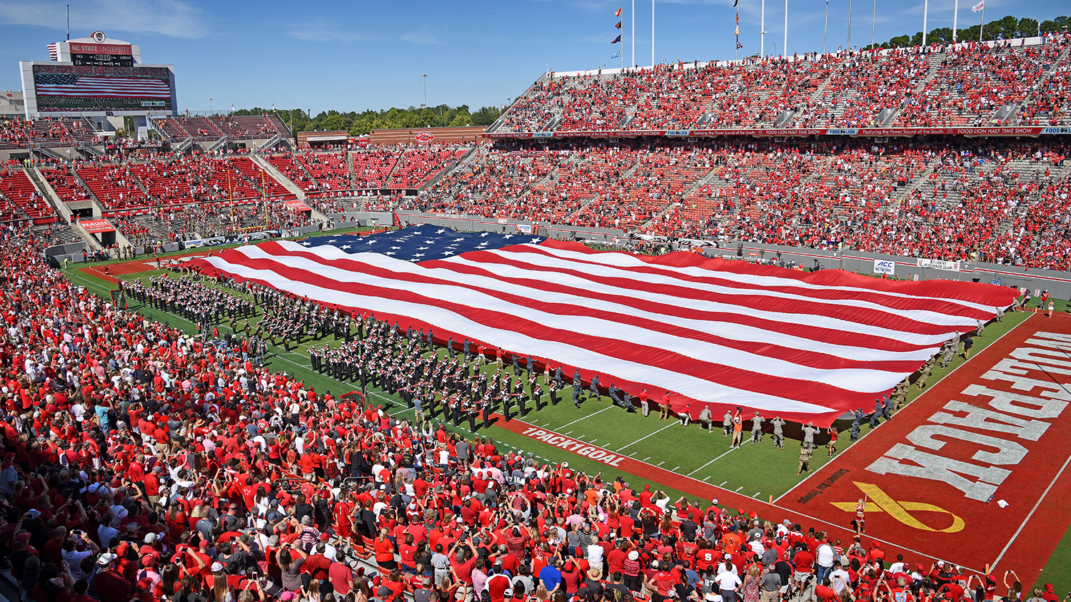 The American flag covers the field during a presentation at half time during the 2017 Military Appreciation Day at Carter-Finley Stadium.
