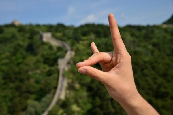 Wolfpack hand sign with the Great Wall of China in the background
