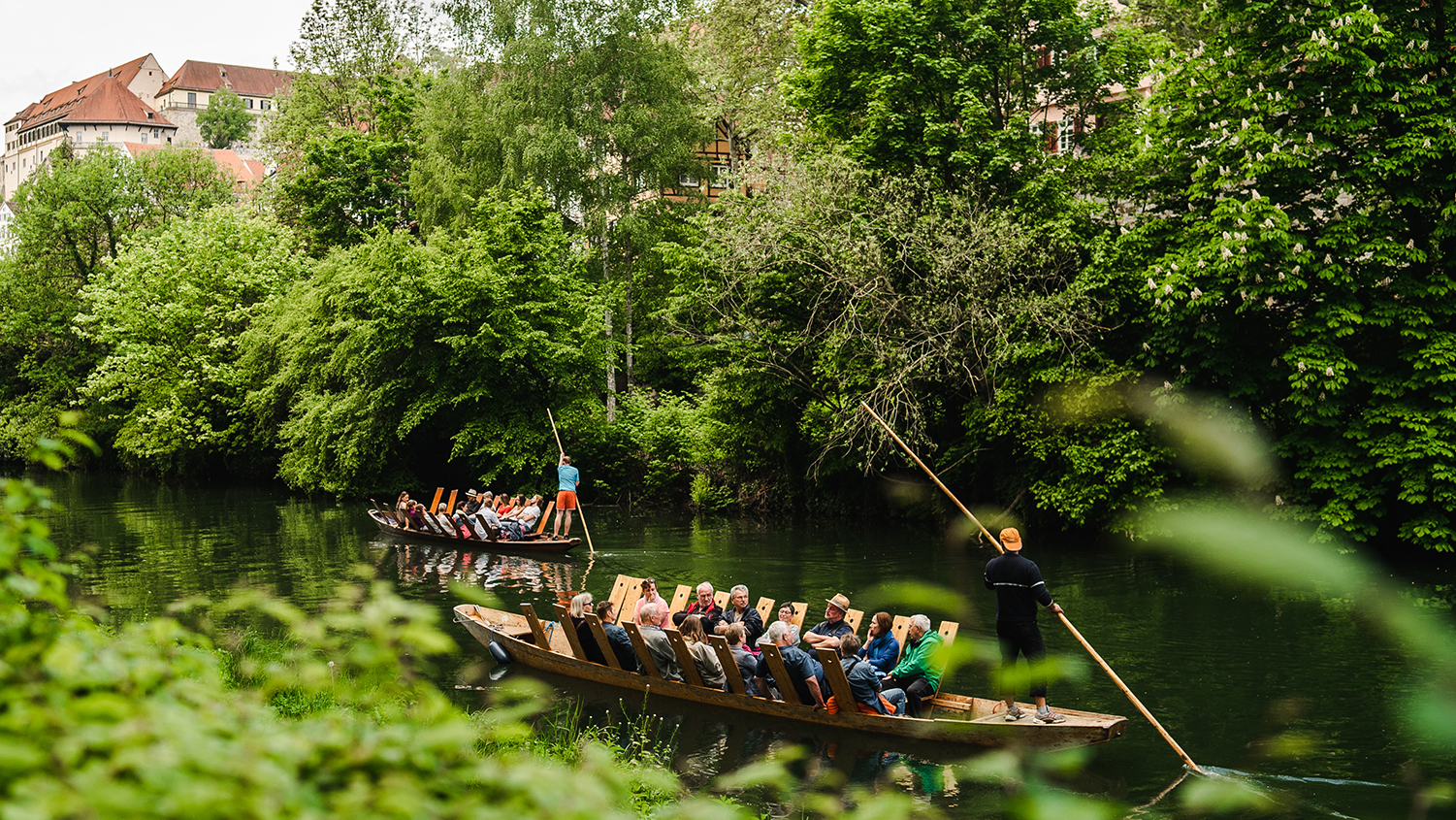 People ride on longboats in a lush river setting