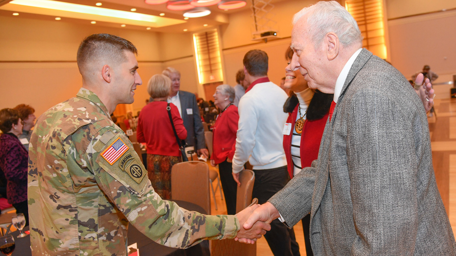 Student in Army uniform shaking professor's hand